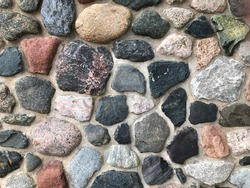 Mosaic stone or rock wall texture pattern in rustic lodge architecture background, bumpy brown white black gray and red stones in cement