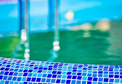 Mosaic swimming pool sidel with blurred stairs and water. Outdoor swimming pool background.