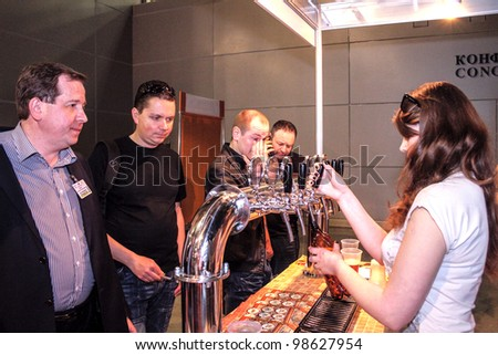 MOSCOW-APRIL 27: Girl pouring beer to glass from beer tap at the international exhibition of market production beer, and low alcohol drinks Brewer on April 27, 2011 in Moscow