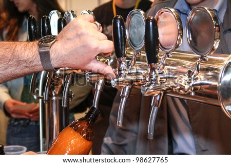 MOSCOW-APRIL 27: Pouring beer to glass from beer tap at the international exhibition of market production beer, and low alcohol drinks Brewer on April 27, 2011 in Moscow