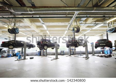 MOSCOW - AUGUST 28: Four black cars raised on lifts in garage Avtomir on Baykalskaya, on August 28, 2012 in Moscow, Russia. Avtomir Group - large car dealer in Russia.