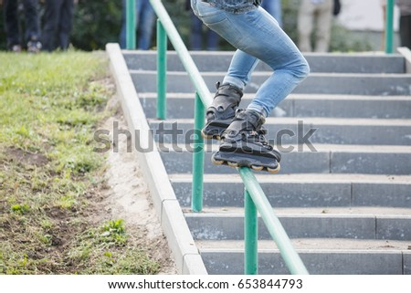 MOSCOW - 15 AUGUST,2015: Outdoor aggressive roller bladers competition S3T contest.Young skater guy grinding handrail on skates.Dangerous extreme skating event.Xsjado skates #653844793