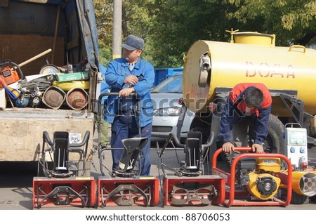 "MOSCOW - AUGUST 30: worker and red manual snow-ploughs  on ""review of technics and the equipment for cleaning"" for preparation for winter in area Butyrsky on August 30, 2011 in Moscow, Russia."