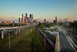 Moscow City, a district of skyscrapers, Moscow, Russia, the sunset is reflected in the buildings, in the foreground - the railway, train, road factory pipes and residential buildings in the distance