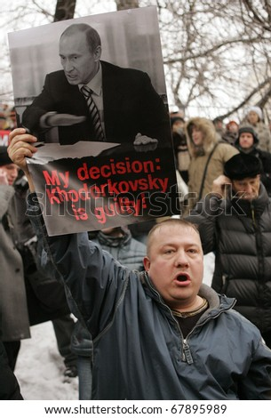 MOSCOW - DECEMBER 27: A Mikhail Khodorkovsky supporter holds up Vladimir Putin's portrait who blamed Khodorkovsky guilty before the start of hearing in the court December 27, 2010 in Moscow, Russia. - stock photo