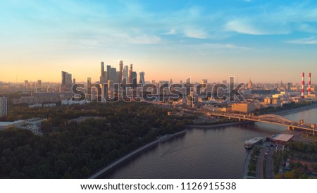 Moscow International Business Center, Moscow-city. A sunset aerial shot of skyscrapers with beautiful evening sky and the Moscow river on the background. Aerial high altitude drone flight.  #1126915538