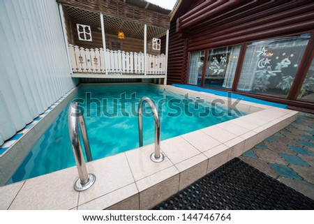 MOSCOW - JAN 1: The pool in the courtyard of log house in Elite Complex Manor Bath at Elk Island on January 1, 2013 in Moscow, Russia.