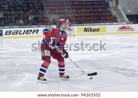 "MOSCOW - JANUARY 31 : Alexander Guskov, defenceman with the puck during a hockey match ""Spartak""(white) -""CSKA""(red) in sports palace ""CSKA"" on January 31, 2012 in Moscow, Russia"