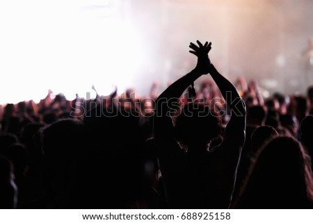 MOSCOW-29 JULY,2017:Concert crowd at music festival outdoor.Young man put hands up to favorite song.Concert audience at entertainment event.Guy claps with hands to the beat