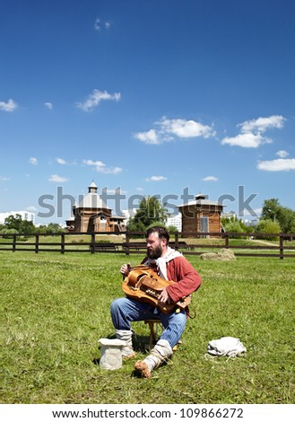 """MOSCOW - JULY 7: Unidentified man in a traditional Russian clothes plays a psaltery during Moscow historical festival """"Times and epoch"""" in Colomenskoe, Moscow on July 7, 2012."""