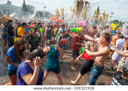 "MOSCOW - JULY 14: Young people shooting and throwing water at each other during flash mob ""Water Battle"" near Peoples Friendship Fountain in VDNKH on July 14, 2012 in Moscow."