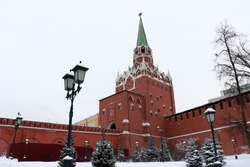 Moscow Kremlin and snow covered fir trees in overcast day, scenic view. Troitskaya tower with red star and vintage street lantern in the Alexander garden, russian winter, landmarks of Russia