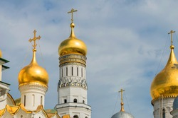 Moscow Kremlin in summer day. Golden domes of Ivan the Great bell tower (left and center) and the dome of Archangel cathedral (right). Spire of Spassky (Saviors) tower in the background.