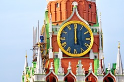 moscow kremlin landmark spasskaya tower clock close up view. Construction works on historical moscow kremlin tower. Worker working on clock renovation. Details of famous architecture building