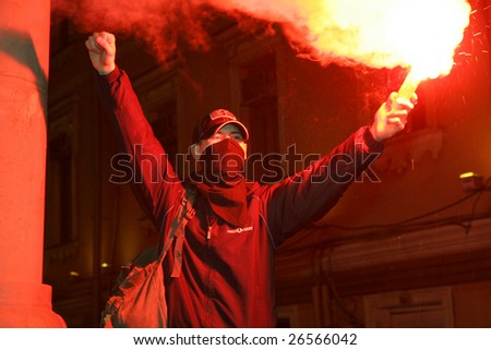 "MOSCOW, MARCH 12: Russian opposition protester carries flare and shouts ""Down with Putin (acting prime minister)"" as he marches along a central street in Moscow, Russia, March 12, 2009."