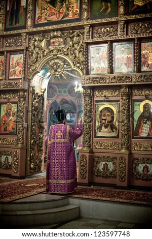 MOSCOW - MARCH 13: The priests reads prayer in front of iconostasis during the Orthodox liturgy with bishop Mercury in High Monastery of St Peter in Moscow on March 13, 2010 in Moscow