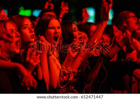 MOSCOW-30 MARCH,2017:Wild crowd of music fans at concert.Young people have fun in nightclub on show of favorite musician.Red lights.Crazy fan woman raving at edm festival.Emotional girl rave in club