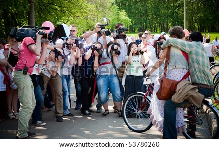 """MOSCOW - MAY 23: Couple posing in front of photographers. """"Voskresnik"""". Festival Bosco di Ciliegi """"Cherry Forest"""".  May 23, 2010 near The Moscow City Palace of children's creativity. Moscow, Russia"""