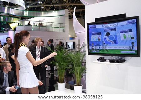 MOSCOW-MAY 11: Girl plays in videos tennis at the international exhibition of the telecommunications industry Sviaz-Expocomm on May 11, 2011 in Moscow