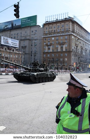 MOSCOW-MAY 6: Police officer looks at the T-90 at the annual dress rehearsal of the Victory Day Parade on May 6, 2012 in Moscow