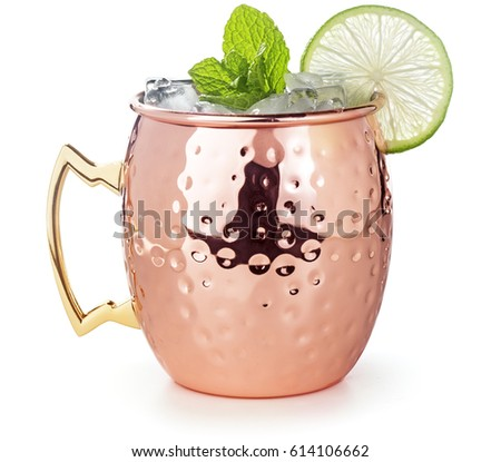 moscow mule cocktail in a copper mug garnished with lime and mint leaves #614106662