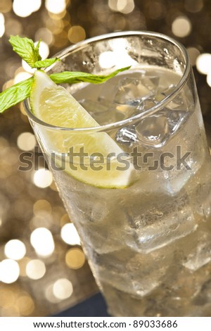 Moscow mule cocktail with lemon garnish in front of a gold glitter background