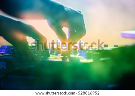 MOSCOW-3 NOVEMBER,2016:Disc jockey mix music on digital midi turntable controller at hip hop party on stage in night club.Hands of DJ playing show,mixing tracks on mixer.Lens flare in green light