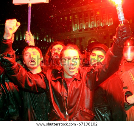 "MOSCOW, NOVEMBER 12: Russian opposition protesters carry flares and shout ""Down with Putin (acting prime minister)"" as they march along a central street November 12, 2010 in Moscow, Russia,"