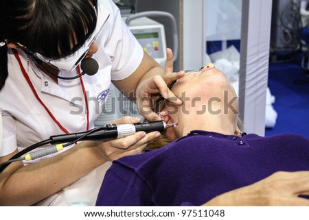 MOSCOW - OCTOBER 26: Beautician performs a laser procedure at the international exhibition of professional cosmetics and beauty salon equipment INTERCHARM on October 26, 2011 in Moscow