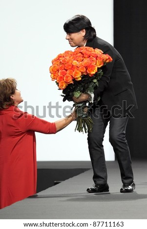 MOSCOW - OCTOBER 26: Fashion designer Valentine Yudashkin is presented flowers during a display of his  collection as part of Fashion Week on October 26, 2011 in Moscow, Russia