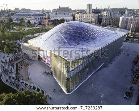 Moscow, Park Zariadye, soaring bridge, city, nature, people, architecture. September 2017.  Multimedia pavilion with glass rooftop. Sunbeams on the glass. Many people walking in the park.