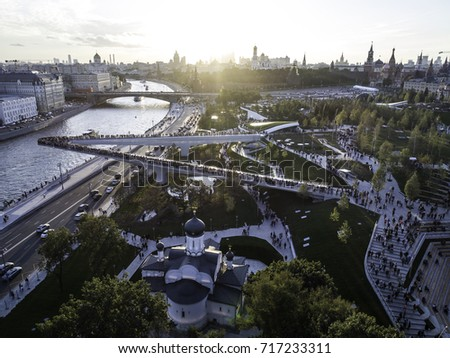 Moscow, Park Zariadye, soaring bridge, city, nature, people, architecture. September 2017.  Green grass, trees and a church in the city centre. Sunset view on the Kremlin.