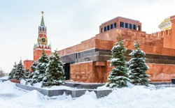 Moscow Red Square in winter, Russia. Lenin's Mausoleum by Moscow Kremlin under snow. This place is a famous tourist attraction of Moscow. The inscription is Lenin. Center of Moscow during snowfall.