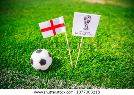 MOSCOW, RUSSIA - APRIL, 24, 2018: england national flag and Official logo of Football FIFA World Cup 2018 in Russia. Green grass, edit space in background. #1077003218