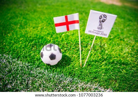 MOSCOW, RUSSIA - APRIL, 24, 2018: england national flag and Official logo of Football FIFA World Cup 2018 in Russia. Green grass, edit space in background. #1077003236