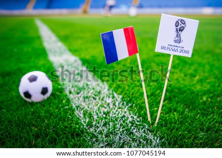 MOSCOW, RUSSIA - APRIL, 24, 2018: France national flag and Official logo of Football FIFA World Cup 2018 in Russia. Green grass, edit space in background. #1077045194