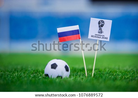 MOSCOW, RUSSIA - APRIL, 24, 2018: Official logo of FIFA World Cup 2018 in Russia and Russian Flag. Green grass, football ball, and stadium in background. Edit space. #1076889572