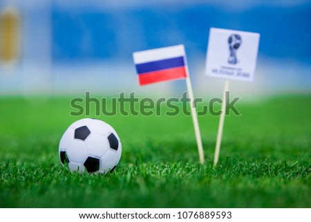 MOSCOW, RUSSIA - APRIL, 24, 2018: Official logo of FIFA World Cup 2018 in Russia and Russian Flag. Green grass, football ball, and stadium in background. Edit space. #1076889593