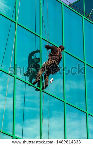 Moscow, Russia - Aug 28, 2019: Window cleaner and glass facade of a skyscraper. Window washing in a high-rise building #1489814333