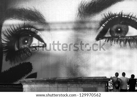 MOSCOW, RUSSIA - AUGUST 22, 2011: Boys staring at a large commercial add promoting cosmetics in Moscow on August 22, 2011. Billboards are the oldest form of advertisements persuading an audience.