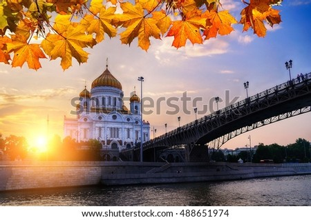 Moscow, Russia- Cathedral of Christ the Savior and Patriarshy bridge. Colorful view of architecture Moscow landmark framed by autumn maple leaves