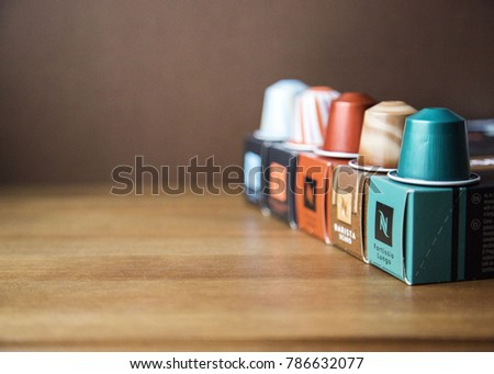 MOSCOW, RUSSIA - JANUARY 03, 2018: Illustrative and Editorial image of Nespresso Boxes and Coffee Capsules on Top of Each Box on Wooden Background