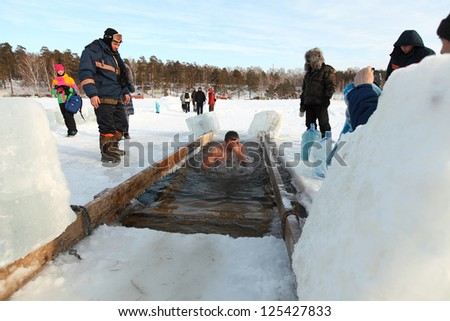 MOSCOW, RUSSIA - JANUARY 19: Swimming in the ice-hole, celebration of Epiphany (Holy Baptism)  in the Orthodox tradition, January 19, 2013 in Moscow, Russia. - stock photo