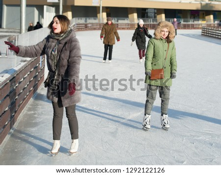 MOSCOW, RUSSIA - JANUARY 22, 2019: Two beautiful girls and people skating in VDNKh on winter sunny day. VDNKh is permanent general purpose trade show and amusement park. #1292122126