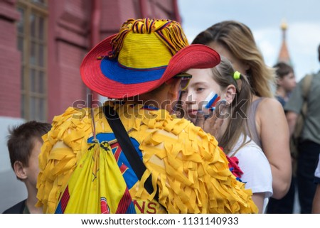Moscow, Russia - July 07, 2018: Colombian sport fan drawing russian flag on the cheek of the young caucasian girl sport fan at the street in the center of  Moscow during soccer world championship. #1131140933