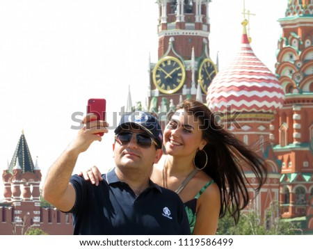 Moscow, Russia - June 2018: Love couple of tourists makes a selfie with smartphone against the Moscow Kremlin and St. Basil's Cathedral. Happy young man and woman during date, romantic trip