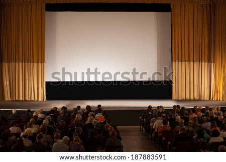 MOSCOW, RUSSIA - MARCH 8, 2013: Audience seated in an auditorium in front of a stage with a screen and open curtains waiting for the start of a film in the Circus of Dancing Fountains Aquamarine