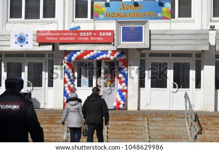 """Moscow, Russia - March 18, 2018: The president election in Russia. People going to the entrance of the polling station. The text means """"Welcome. Polling station N..."""""""