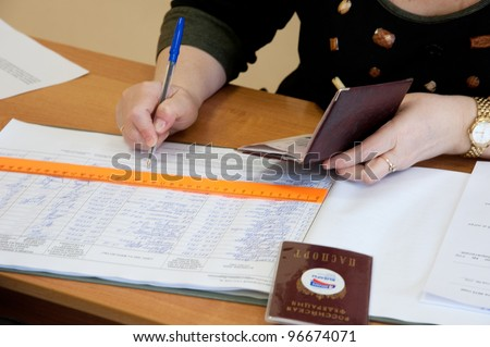MOSCOW, RUSSIA - MARCH 4: Woman write name of voters in notebook on election of Russian President on March 4, 2012 at the local election commission in Moscow.