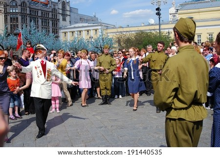 MOSCOW, RUSSIA - MAY 09: A senior war veteran in white jacket dances with a redhead woman on the Theater Square, by the Bolshoy Theater. Victory Day celebration on May 09, 2013 in Moscow.